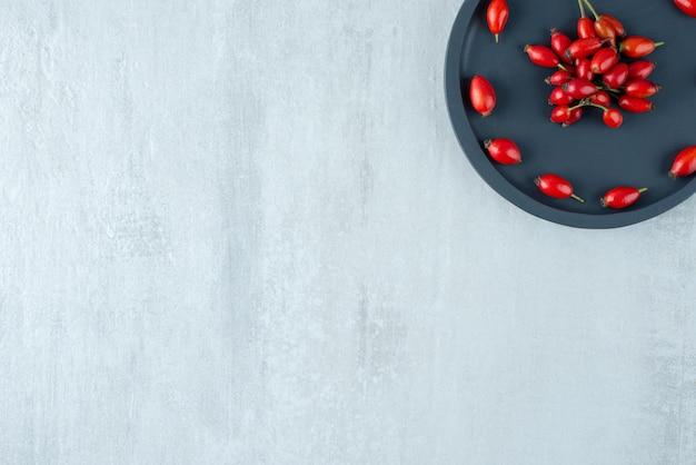 Świeżo zebrane owoce dzikiej róży na czarnej tablicy.