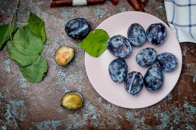 Świeżo zebrane śliwki w płycie ceramicznej na ciemnej powierzchni