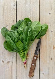 Świeżo zebrany organiczny szpinak na ciemnym drewnianym stole, zielone warzywa z kroplami wody,