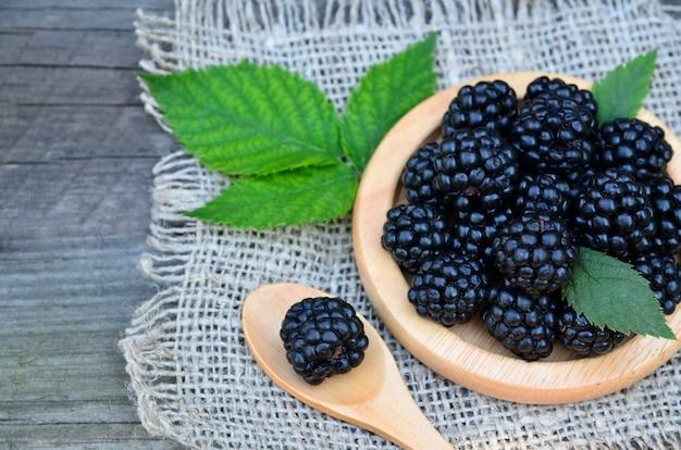 Świeżo zerwane dojrzałe jeżyny na drewnianym talerzu na stole zdrowe odżywianie, wegańskie jedzenie lub dieta koncepcja selektywna ostrość