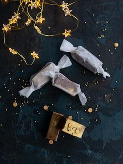 Świeżo-złote karmelowe cukierki toffi w białej księdze na niebieskim ciemnym tle z girlandą w postaci świecących gwiazd.