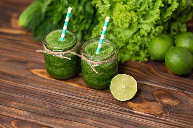 Świeżo zmiksowany koktajl z zielonych owoców w szklanym słoiku ze słomką