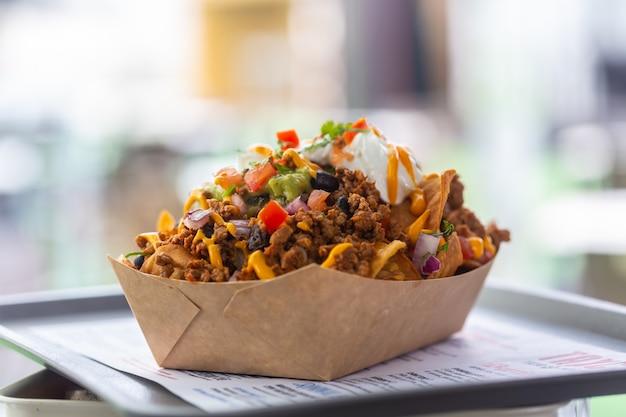 Świeżo zrobiona salsa nachos na tacy w papierowym talerzu w ulicznej kawiarni