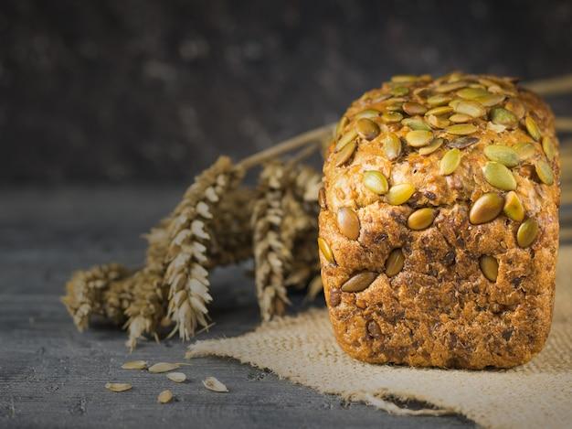Świeżo zrobiony chleb z mąki pszennej z pestkami dyni, słonecznikiem i sezamem na stole