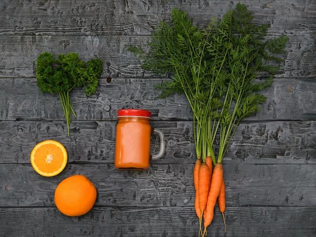 Świeżo zrobiony koktajl marchewkowy, wiązka marchewki i dwie pomarańczowe na rustykalnym stole