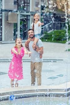 Świeżość wody. radosna szczęśliwa rodzina patrząc na krople wody, stojąc w pobliżu fontanny