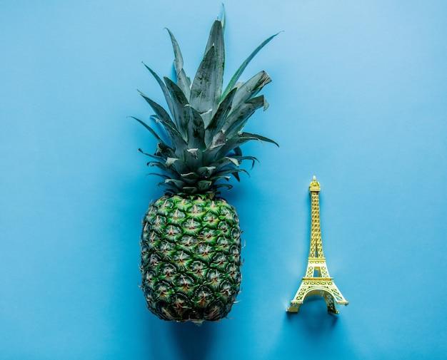 Świeży ananas i pamiątka wieża eiffla na niebieskim tle. powyżej widok