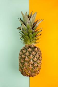 Świeży ananas na lodowym błękitnym i pomarańczowym tle