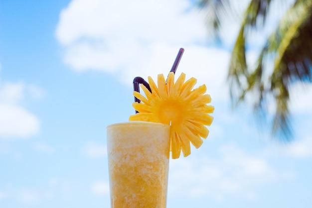 Świeży ananas na tle nieba i palm