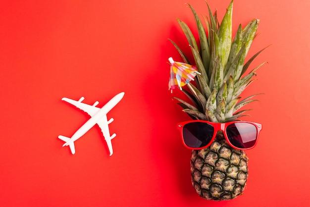 Świeży ananas nosi czerwone okulary przeciwsłoneczne z modelem samolotu