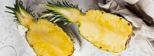 Świeży ananas pokroić na pół na szarym tle starego betonu. koncepcja lato. kreatywne mieszkanie leżało z miejscem na kopię. widok z góry