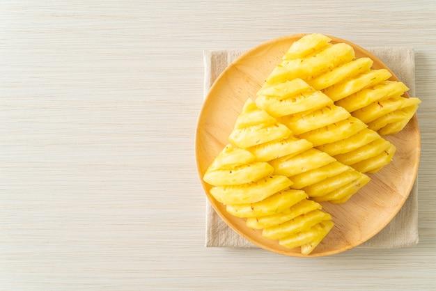 Świeży ananas pokrojony na drewnianym talerzu