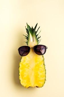 Świeży ananas pokrojony w dwie części, notatnik lub szkicownik i okulary przeciwsłoneczne na żółtym tle. koncepcja lato. kreatywne mieszkanie leżało z miejscem na kopię. widok z góry