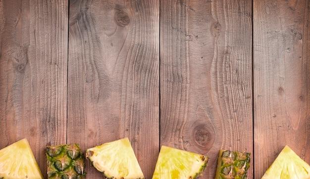 Świeży ananas pokrojony w plasterki z całością. na drewnianym tle.