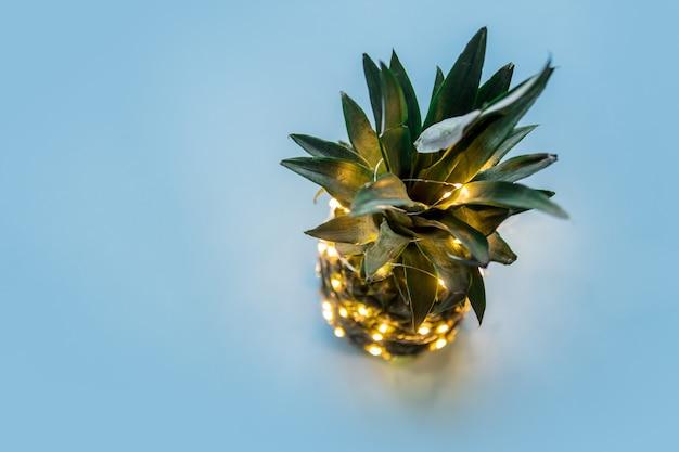 Świeży ananas z czarodziejskimi światłami na niebieskim tle.