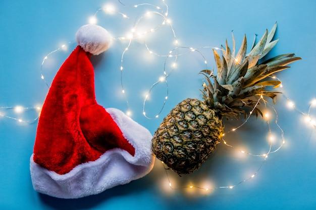 Świeży ananas z fairy lights i boże narodzenie kapeluszem na niebieskim tle.