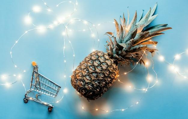 Świeży ananas z fairy lights i koszyk na niebieskim tle.