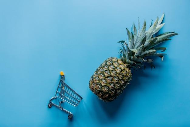 Świeży ananas z koszykiem na niebieskim tle.