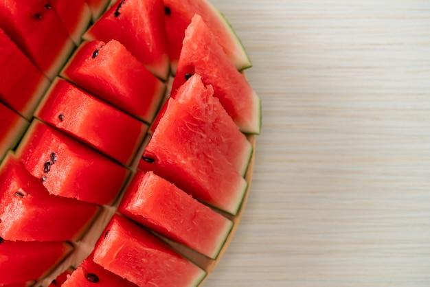 Świeży arbuz pokrojony na drewnianym talerzu