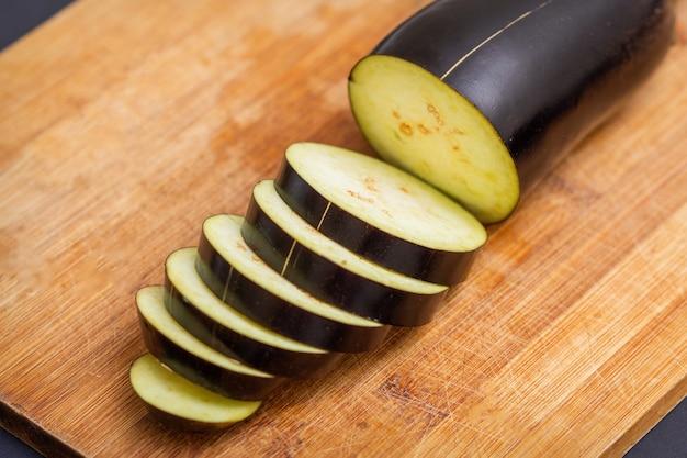 Świeży bakłażan pokrojony na drewnianą deskę do krojenia na czarnym tle. składniki do gotowania