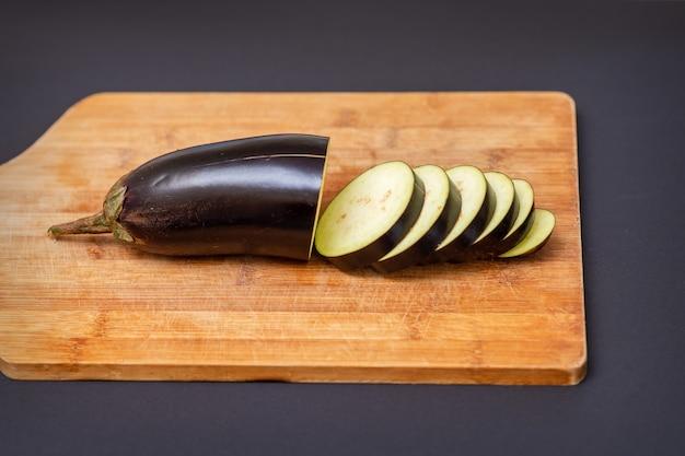 Świeży bakłażan pokrojony na drewnianą deskę do krojenia na czarnym tle.