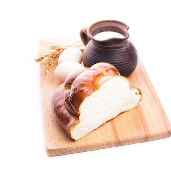 Świeży bochenek chałki z mlekiem i jajkami na drewnianej desce