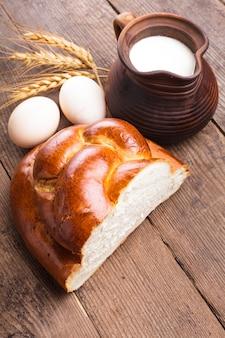 Świeży bochenek chałki z mlekiem i jajkami na stole