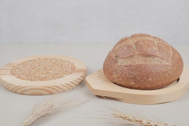 Świeży bochenek chleba z pszenicy na drewnianej tablicy