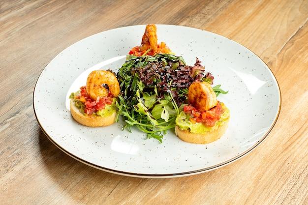 Świeży bruschetta z garnelą i sałatką na białym talerzu na drewnianym. kuchnia włoska. owoce morza. przystawka przed lunchem
