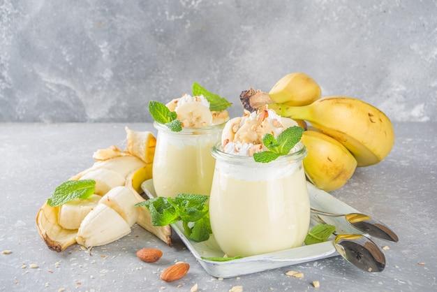 Świeży budyń bananowy na śniadanie, jogurt bananowy. słodki deser w szklankach z plastrami banana i orzechami, surowa wegetariańska przekąska