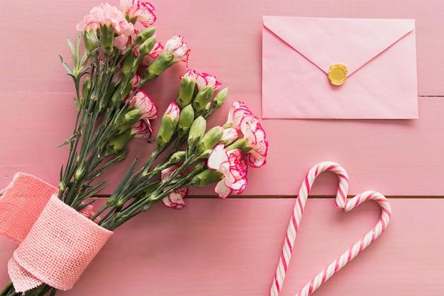 Świeży bukiet kwiatów z wstążką w pobliżu koperty i cukierki laski