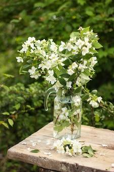 Świeży bukiet kwitnącego pachnącego jaśminu w szklanym wazonie w stylu rustykalnym na starym drewnianym stole