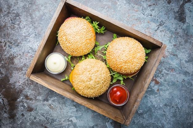 Świeży burger domowej roboty w pudełku z ostrym sosem i ziołami na ciemnym kamieniu