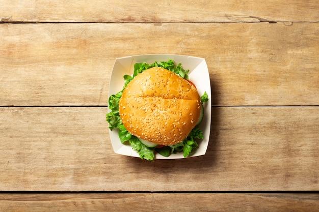 Świeży burger na lekkim drewnianym stole