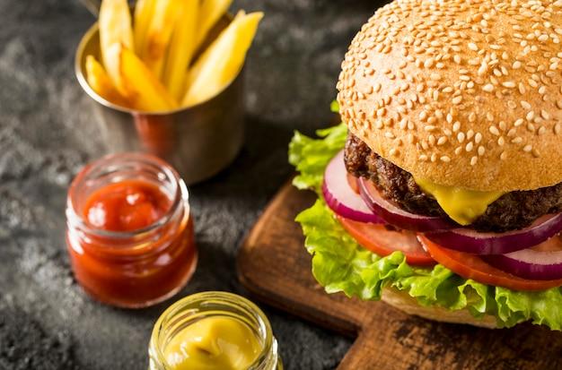 Świeży burger pod wysokim kątem z frytkami i sosami