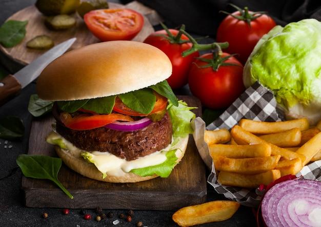 Świeży burger wołowy z sosem i warzywami i frytkami ziemniaczanymi na kamiennej kuchni.