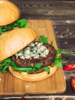 Świeży burger z serem pleśniowym i rukolą na rustykalnym drewnianym tle