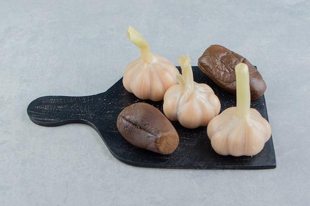 Świeży cały czosnek i ogórek konserwowy na desce do krojenia na marmurowej powierzchni