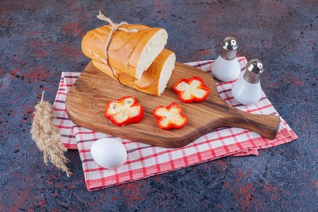 Świeży chleb biały pokrojony na desce i jajko na twardo.