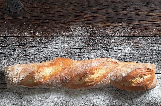 Świeży chleb ciabatta na ciemnym tle drewnianych, widok z góry. miejsce na tekst
