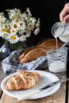Świeży chleb i rogalik z mlekiem na drewnianym stole. bukiet stokrotek. rustykalny