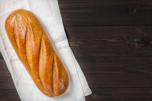 Świeży chleb na płótnie przeciw ciemnemu drewnianemu tłu