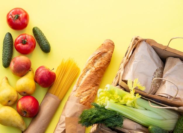 Świeży chleb organiczny, warzywa, warzywa, warzywa i owoce, płatki zbożowe i makaron na żółtym stole. koncepcja żywności ekologicznej gospodarstwa. widok z góry. leżał na płasko