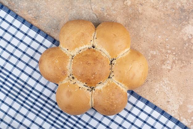 Świeży chleb w kształcie kwiatu na tle marmuru
