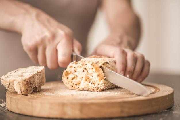 Świeży chleb w rękach zbliżenie na stare drewniane tła