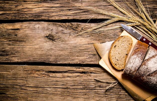Świeży chleb z kłosami żyta. na drewnianym stole. wolne miejsce na tekst. widok z góry