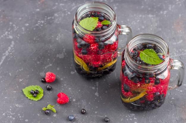 Świeży chłodny napój detoksykacyjny z malinami, jagodami i kiwi w słoiku z masonem. lemoniada w szklance z miętą. pojęcie właściwego odżywiania i zdrowego odżywiania. dieta fitness skopiuj miejsce na tex