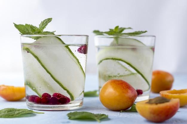Świeży chłodny napój detox z ogórkiem, jagodami i brzoskwiniami lub aprikotami.
