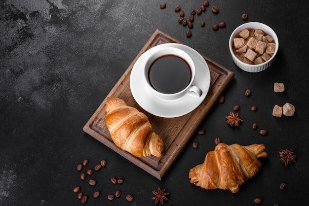 Świeży, Chrupiący, Pyszny Francuski Rogalik Z Filiżanką Aromatycznej Kawy. Pobudzające śniadanie Premium Zdjęcia