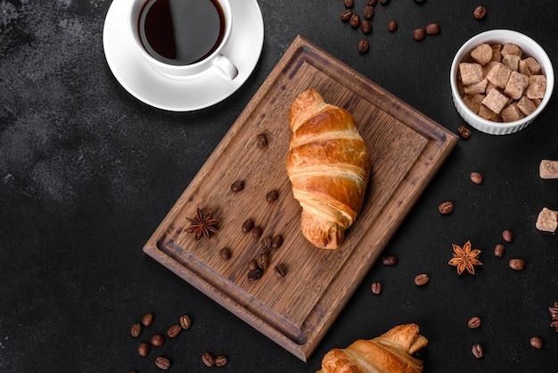 Świeży, chrupiący, pyszny francuski rogalik z filiżanką aromatycznej kawy. pobudzające śniadanie